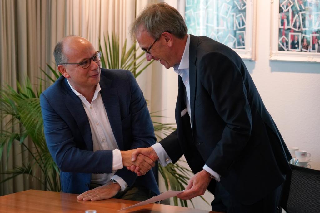Jaap Hop (links, Rexcom) en John Quist (rechts, CEO Unica) schudden elkaar de hand
